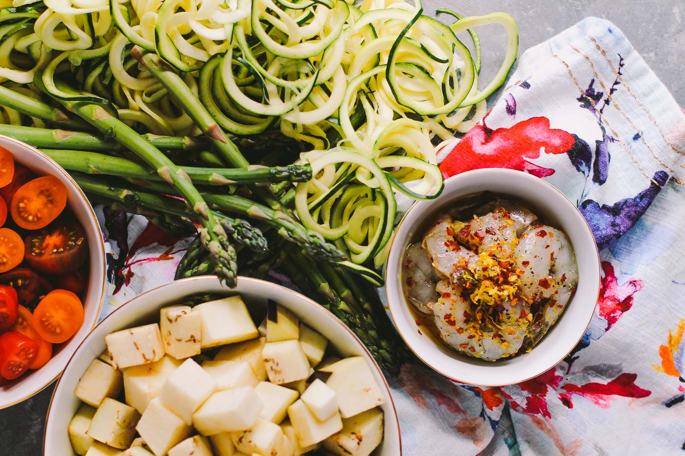 zoodles tossed into a garlic-infused olive oil with lemon & loads of summer vegetables. topped off with shrimp, grated cheese, and a good sprinkle of crushed red chili, these aglio olio zoodles are going to be your new favorite this summer! | gluten free, healthy recipe, summer food, summer party, vegetables, farmers market recipe, easy recipe |