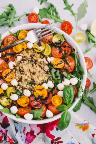 a simple summer salad straight from my mom's kitchen! a bed of peppery fresh arugula is topped with israeli couscous & perfectly ripened tomatoes & drizzled with a simple homemade lemon vinaigrette & reduced balsamic. ready in less than 15 minutes, this simple summer salad is the perfect dish to share at a summer party or to serve for a healthy, fast weeknight dinner!