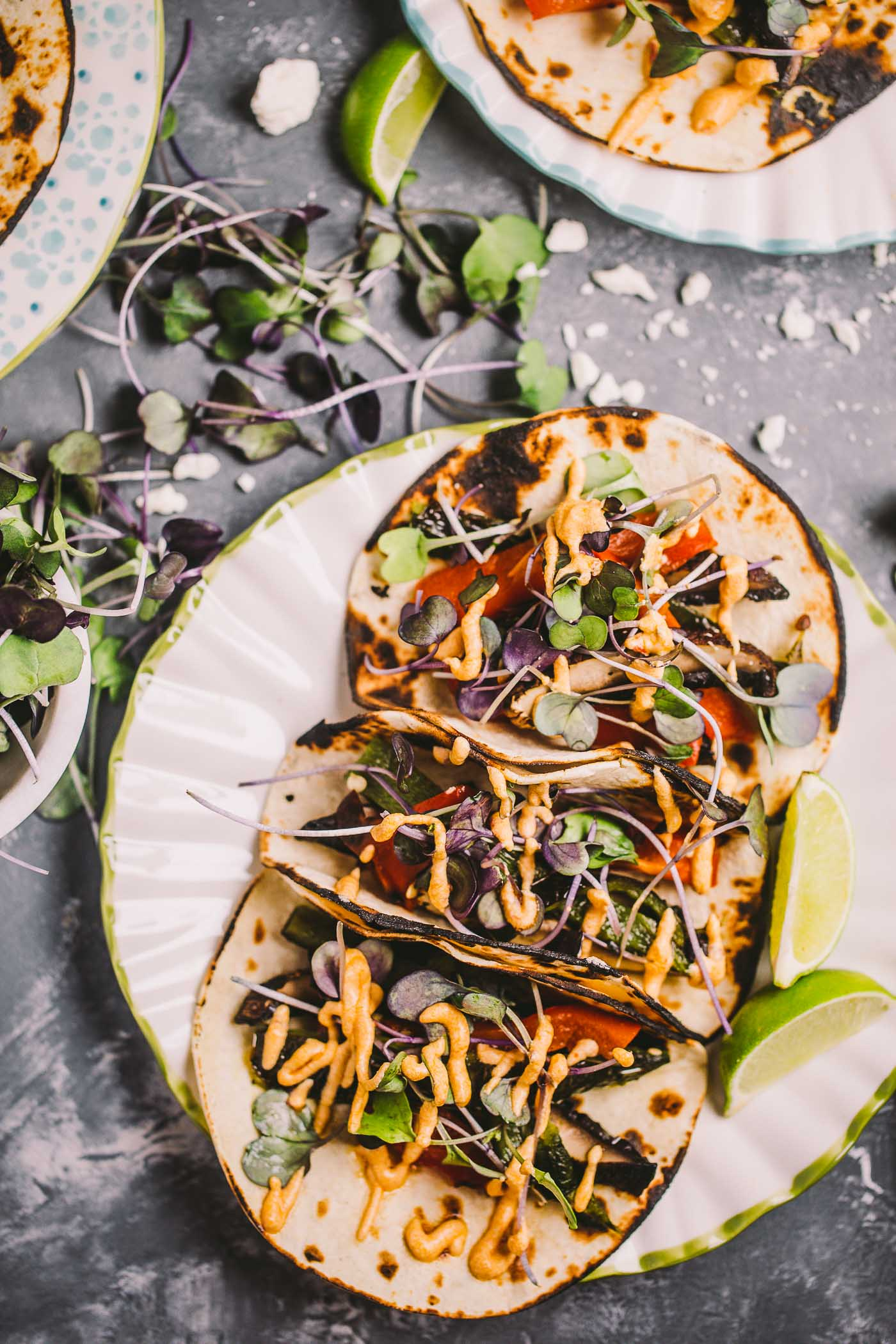 grilled vegetarian tacos loaded with end of summer vegetables (poblanos, red bell pepper, portobello mushrooms) that have been roasted over the direct flame on the grill. topped with a handful of spicy microgreens & a creamy, smoky, tangy goat cheese spread full of chipotle & lime. only thing missing is margs & guac!