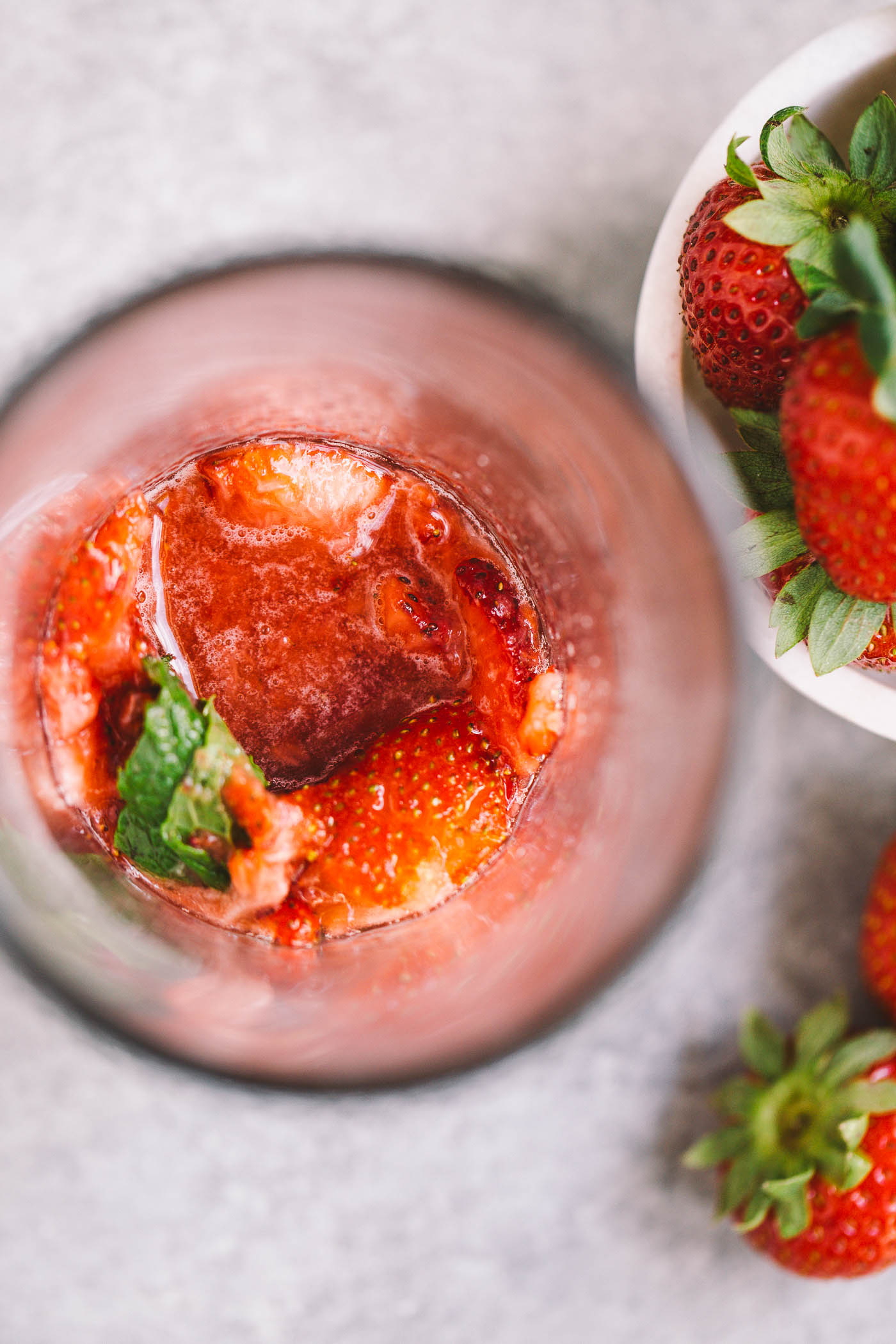 classic mojitos get a spicy strawberry twist in this easy cocktail recipe for spicy strawberry mojitos! fresh strawberries muddled with lime juice, mint, & spicy rum for the perfectly balanced spicy & sweet cocktails. these spicy strawberry mojitos will be your new favorite! #mojitos #easycocktail #cocktailrecipe #strawberrymojitos #spicystrawberrymojitos #playswellwithbutter