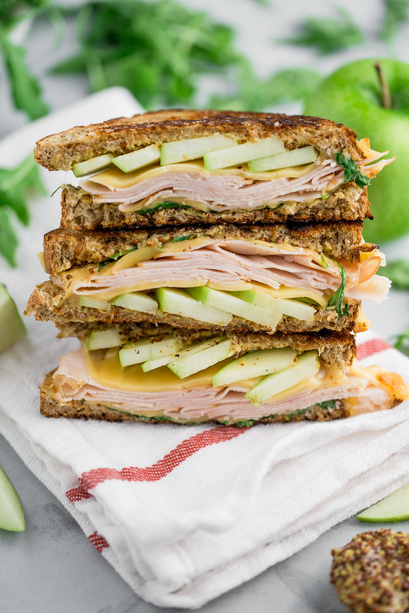 autumn grilled cheese sandwiches stuffed with fall flavor! hearty whole-grain bread slathered in whole grain mustard & sandwiched around melty gouda, smoked turkey, & crisp granny smith apples. the only thing missing is a big dunk into a bowl of tomato soup! #playswellwithbutter #comfortfood #grilledcheese #grannysmith