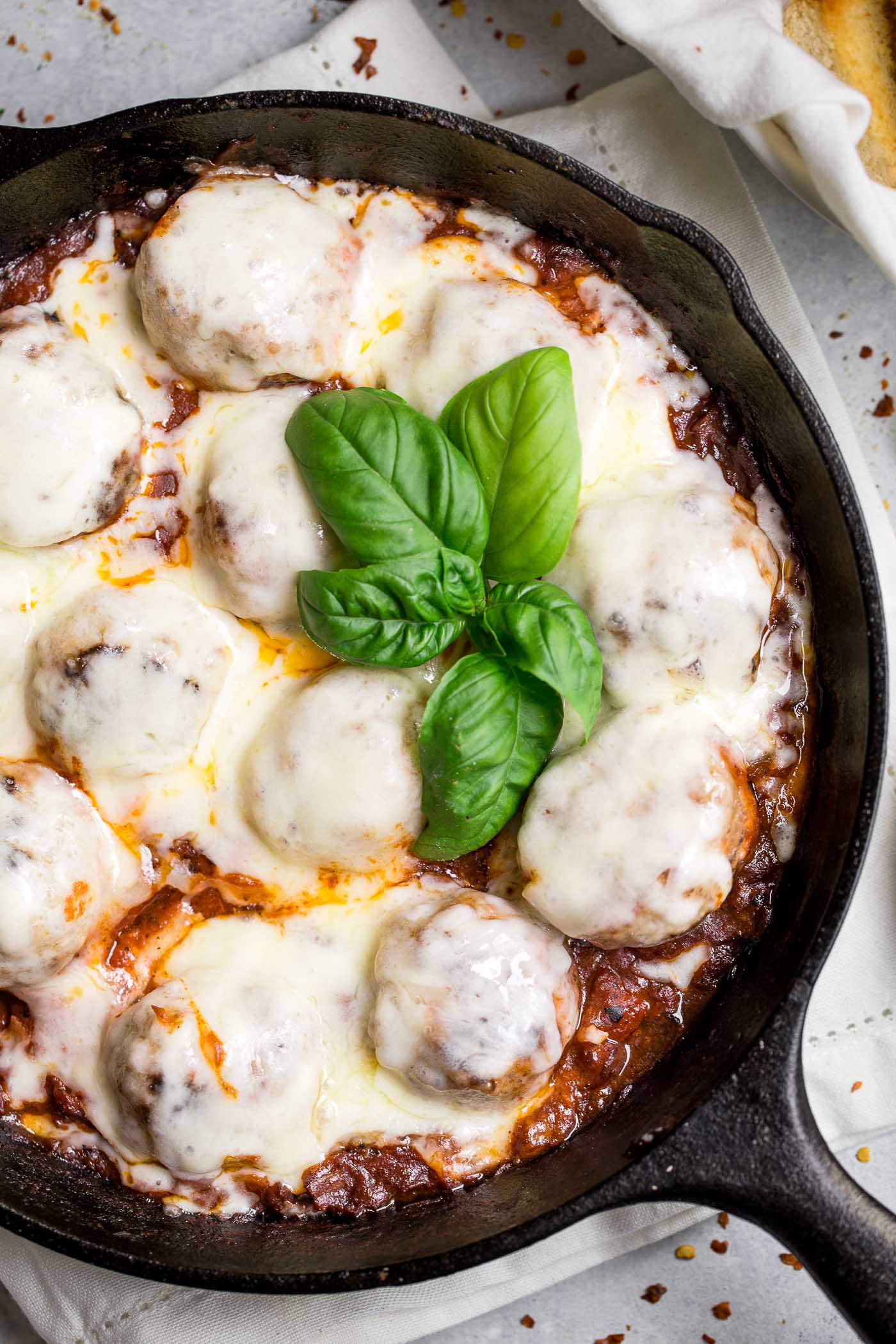skillet chicken parmesan meatballs are an easy & healthy weeknight skillet dinner that easily doubles as the perfect game day treat. the best tender chicken meatballs are seared cooked in a quick homemade tomato sauce & covered in melty provolone cheese. one-pan weeknight dinner for the win! #playswellwithbutter #chickenparmesan #chickenmeatballs #easyrecipe #healthyrecipe #gamedaysnack