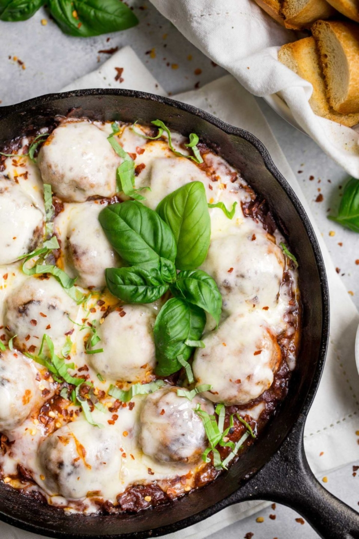 an easy & healthy weeknight skillet dinner that easily doubles as the perfect game day treat. the best tender chicken meatballs are seared cooked in a quick homemade tomato sauce & covered in melty provolone cheese. one-pan weeknight dinner for the win! #playswellwithbutter #chickenparmesan #chickenmeatballs #easyrecipe #healthyrecipe #gamedaysnack
