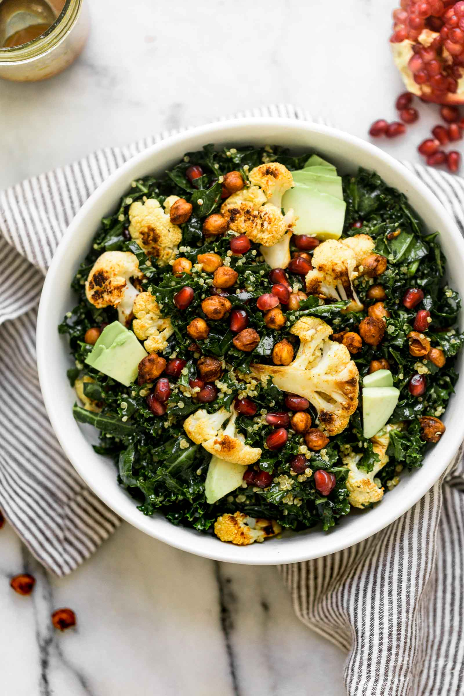 a nourishing & filling winter salad, this winter glow bowl is loaded with the best feel-good winter ingredients: roasted cauliflower, pomegranate arils, avocado, & kale, which all get tossed together in a homemade curry vinaigrette with spiced roasted chickpeas. winter salads have never looked this good! #salad #mealprep #saladrecipe #kalesalad #curryvinaigrette #roastedcauliflower #roastedchickpeas #playswellwithbutter