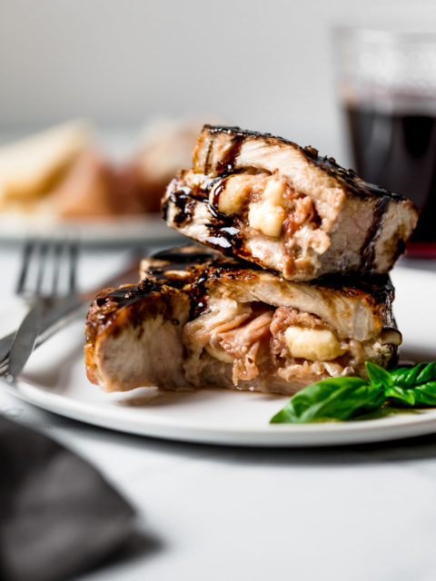 these stuffed grilled pork chops look SO fancy, but they are so easy to throw together! bone-in pork chops get stuffed with prosciutto & asiago cheese, then they're cooked to perfection on the grill until the pork is juicy & the cheese is melty, & served with a drizzling of balsamic glaze. a total showstopper perfect for easy weeknight dinners or your next summer BBQ party! #playswellwithbutter #grilledporkchops #stuffedporkchops #porkchopsrecipe #boneinporkchops #prosciutto #asiago #easygrillingrecipes #summerdinnerrecipes