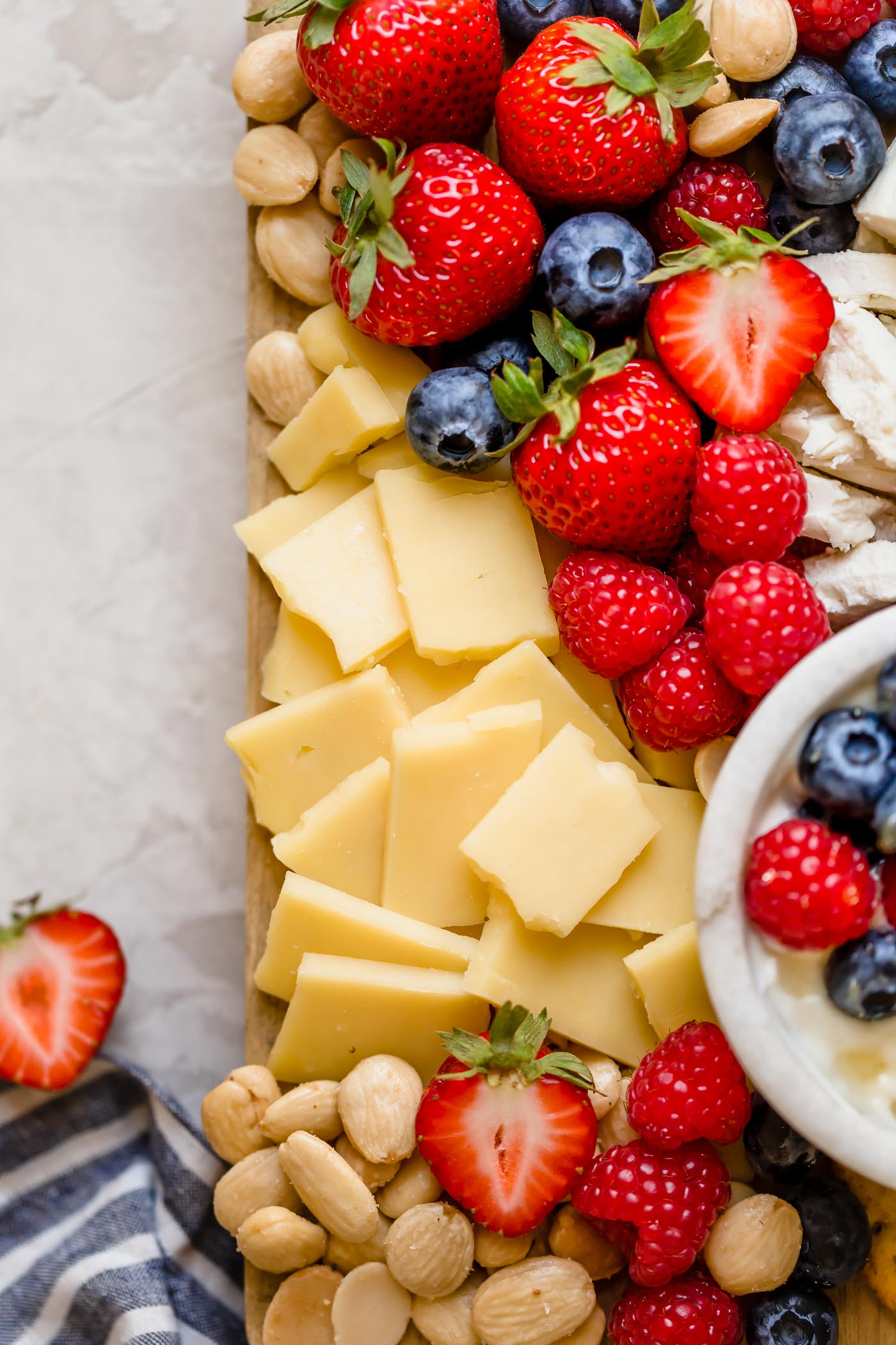 a summer berry cheese board filled with strawberries, raspberries, blueberries, & the perfect cheeses to pair with cheese boards. this summer berry cheese board is an easy & fun appetizer or snack to serve at parties & barbeques all summer long! #playswellwithbutter #summerberrycheeseboard #cheeseboard #summercheeseboard #cheeseboardidea #appetizer #appetizersforparty #easyappetizers #makeaheadappetizers