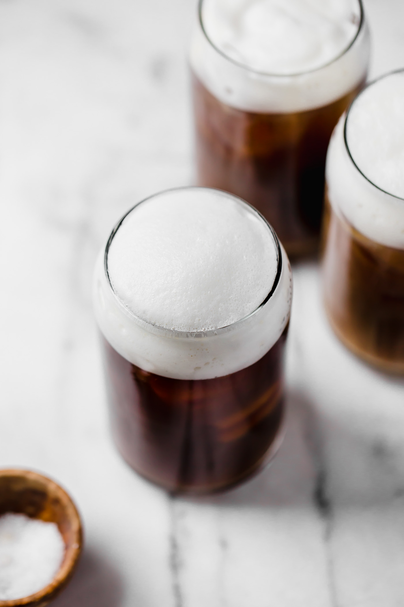 an easy & natural recipe for homemade starbucks salted cream cold foam cold brew with only 4-ingredients! cold brew coffee, lightly sweetened with maple syrup, topped with a creamy salty-sweet cold foam, this salted cream cold foam cold brew coffee is the perfect salty-sweet coffee drink! #playswellwithbutter #saltedcreamcoldfoamcoldbrewcoffee #coldbrew #coldbrewcoffeerecipe #icedcoffee #easycoffeerecipe #starbucksdrinks #starbucksrecipe