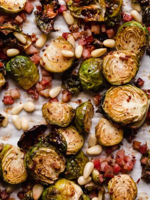 maple mustard roasted brussels sprouts with pancetta, parmesan & pine nuts! brussels sprouts tossed in a simple sauce made of maple syrup & two kinds of mustard with pancetta (italian bacon!) & roast til they're perfectly caramelly & crispy. served with pine nuts & parmesan, these maple roasted brussels sprouts are perfect for a holiday dinner & easy enough for weeknight dinners! #playswellwithbutter #roastedbrusselssprouts #roastedbrusselssproutswithbacon #easysidedish #thanksgivingsidedish