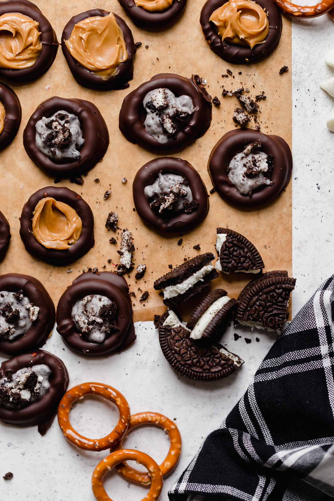 stuffed dark chocolate dipped pretzels. holiday pretzel rounds get filled with peanut butter, salted caramel, oreos, peppermint candies, or any other fillings you love, & covered in dark chocolate. these stuffed dark chocolate dipped pretzels take chocolate covered pretzels to the next level, & they're the perfect easy no-bake treat to add to your christmas cookie plates this year! #playswellwithbutter #chocolatepretzels #nobakedessert #chocolatedippedpretzels #stuffedpretzels #howtomakechocolatepretzels
