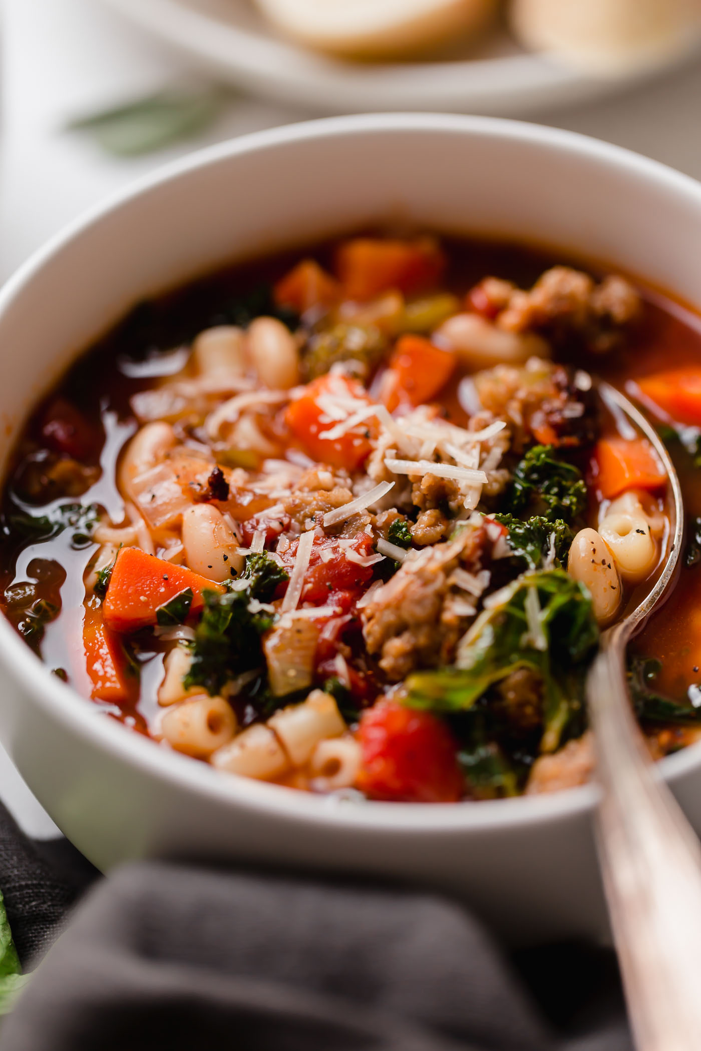 a hearty minestrone soup recipe, made with italian sausage, veggies, beans, kale, & a garlic & herb infused broth. this minestrone soup is comforting, rich, & the perfect cozy recipe to make all winter long. the ultimate minestrone soup! #playswellwithbutter #minestronesoup #heartysouprecipes #heartymeals #souprecipes #comfortfood #comfortfooddinners #soup #italianrecipes #italiansoup