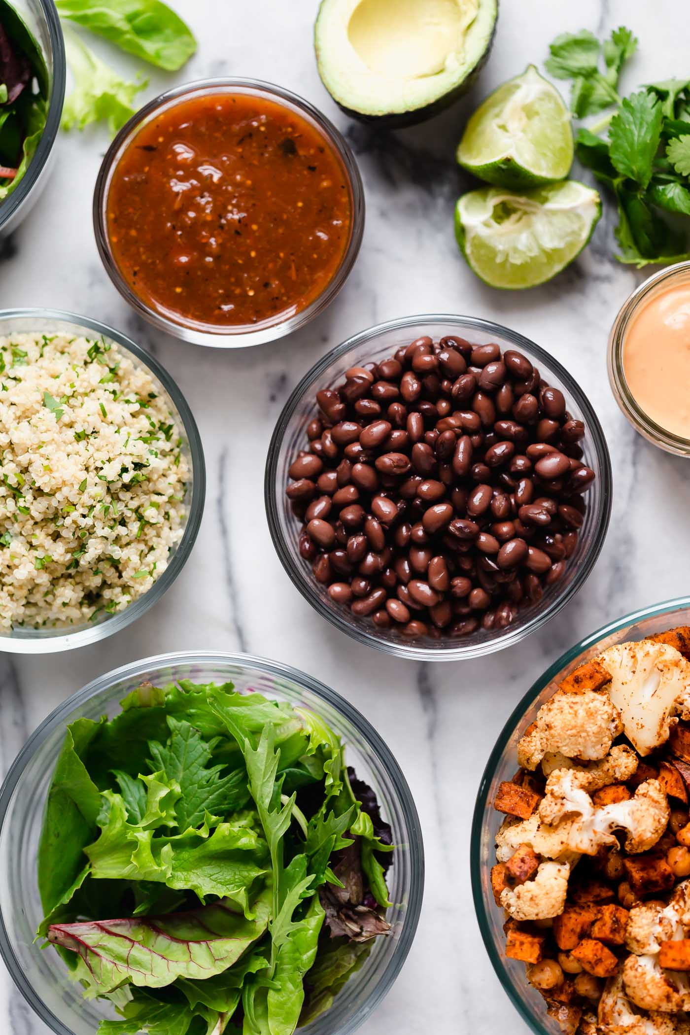 an easy roasted veggie vegan taco salad recipe! this plant-based taco salad is piled high with roasted cauliflower, sweet potatoes, & chickpeas, plus any other taco toppings you love, & served with a homemade smoky & creamy cashew vegan taco salad dressing that's so good you'll want to eat it by the spoonful! the perfect easy meatless monday dinner, or healthy lunch to meal prep for the week. #playswellwithbutter #vegantacosalad #healthytacosalad #vegansalad #veganrecipes #plantbasedrecipes