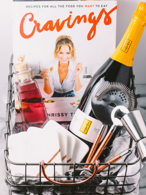 homemade holiday gift basket for the kitchenista in your life | a plays well with butter holiday gift basket series | a homemade gift basket perfect for the young & trendy person who is just starting to take interest in food & dining. this gift basket features some prosecco for a festive holiday cocktail, on-trend bar gadgets, & chrissy teigen's cookbook.