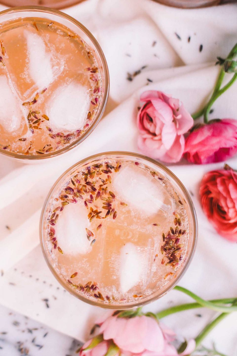lavender lemonade rosé cocktails taste like summer! pair your favorite dry rosé with a tangy & sweet homemade lavender lemonade & topped with sparkling water. be prepared to sip on these lavender lemonade rosé cocktails all summer long. these simple pink drinks are perfect for mother's day, bridal showers, girls night, or just having a drink or two on a friday night while your guy drinks beer. seriously pretty, seriously delicious, seriously easy!   cocktail recipe, lavender cocktail, rose cocktail, girls night, summer drink  