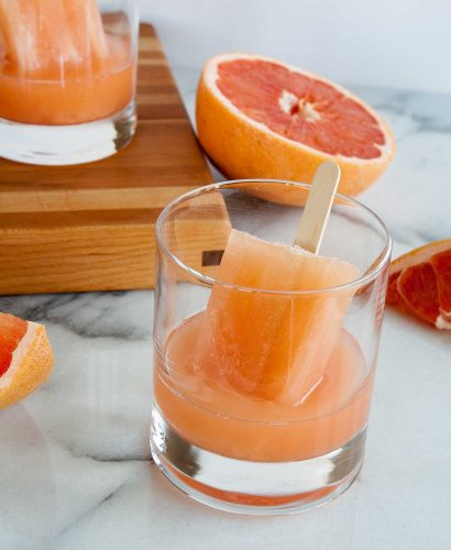 greyhound boozy popsicles are perfect for summer! tart fresh grapefruit juice is balanced by a homemade rosemary simple syrup, these alcohol popsicles are going to be your new go-to for summer entertaining! | summer drinks, homemade alcohol popsicle recipe, boozy popsicle recipe, girls night, summer party, greyhound cocktail, vodka cocktail |