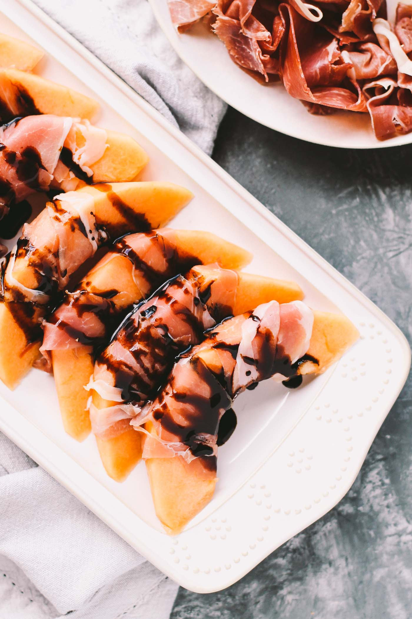 a three-ingredient recipe for prosciutto wrapped cantaloupe topped with balsamic glaze. this appetizer is perfectly balanced, super simple, & most importantly - so delicious! prosciutto-wrapped cantaloupe with balsamic glaze are perfect for summer parties & easy entertaining on hot summer nights. | prosciutto, easy appetizer for a crowd, summer food, summer party, healthy appetizer recipe, make ahead appetizer, girls night recipe, date night recipe |