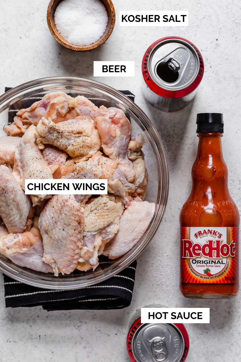 Grilled chicken wings ingredients arranged on a white surface - a bowl of chicken wings, a bottle of Frank's RedHot hot sauce, a can of Surly Furious Double IPA beer, & a small wooden bowl of kosher salt.
