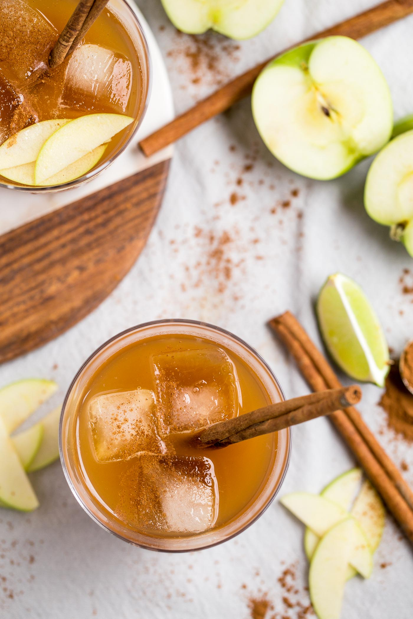 easy & cozy bourbon ginger cider cocktails perfect for autumn! the bold flavor of a nice bourbon is perfectly balanced out by warming notes of a good apple cider & ground cinnamon, the spice of a strong ginger beer, & the bright tang of fresh lime. you will love making these bourbon ginger cider cocktails for your friends & family all autumn long! #playswellwithbutter #easycocktailrecipe #bourbon #autumncocktail #fallcocktail