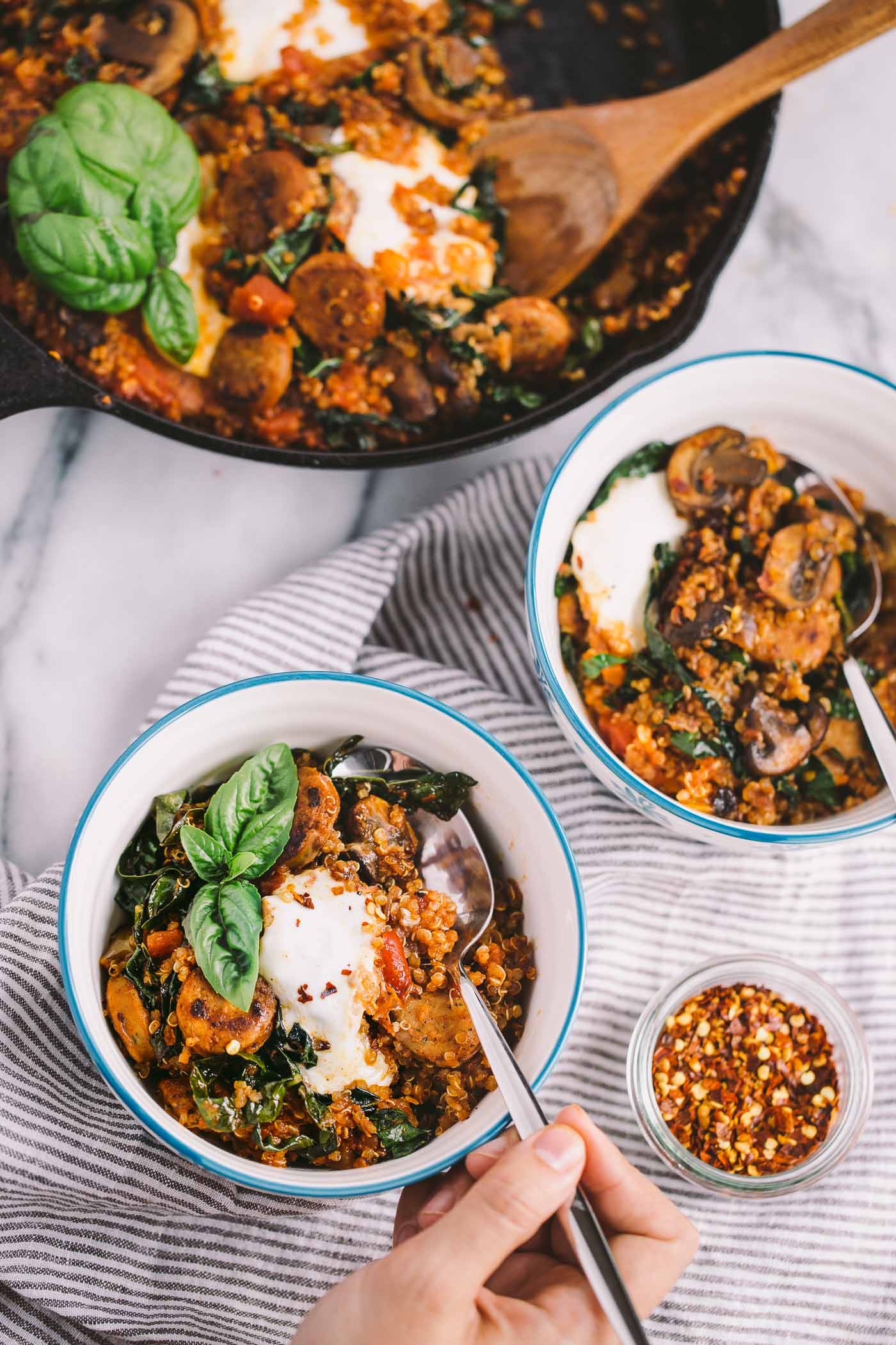 a 15-minute skillet dinner with quinoa, kale, trader joe's chicken sausage, & trader joe's arrabiata sauce. weeknight cooking could not be easier (or more delicious!) than this 15-minute trader joe's skillet! #playswellwithbutter #skilletdinner #easydinnerrecipe #traderjoes #traderjoesrecipe #skilletrecipe #healthydinnerrecipe