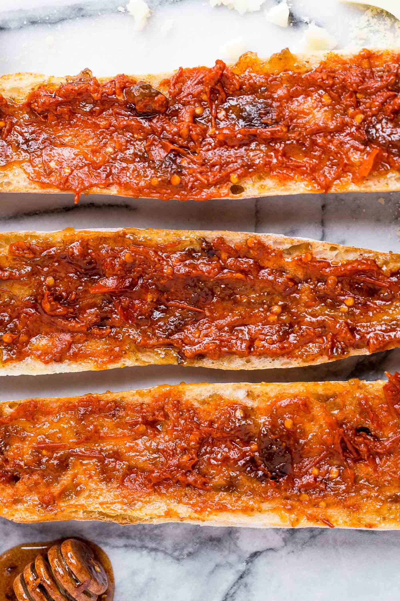 easy chorizo french breads with manchego, fig spread, & harissa, & covered in big fat drizzles of homemade spicy paprika honey. an easy & elegant appetizer! an easy & elegant appetizer or snack, perfect for holiday entertaining! #playswellwithbutter #chorizo #harissa #manchego #holidayparty #cocktailparty #appetizer