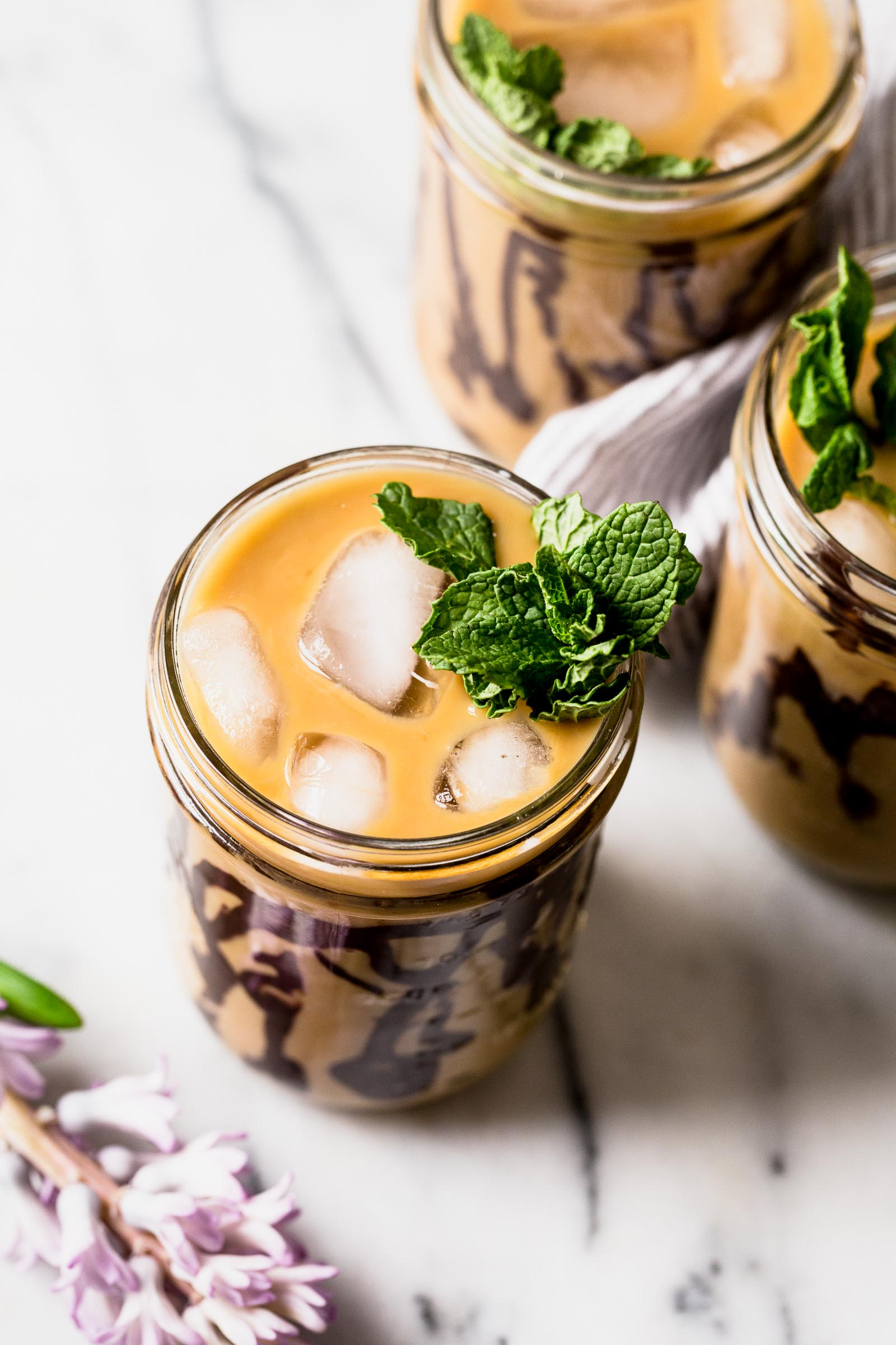 an easy & refreshing fresh mint cold brew iced coffee served with swirls of homemade dark chocolate syrup. the perfect springtime pick-me-up! #coldbrew #icedcoffee #minticedcoffee #dunkindonuts #dunkindonutsicedcoffee #easyicedcoffee #icedcoffeerecipe