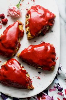 tender & flaky scones bursting with dark chocolate chunks & topped with the perfect raspberry glaze. raspberry dark chocolate chunk scones are perfect for galentine's day, a wedding shower, baby shower, or any ladies' brunch! #scones #sconerecipe #galentinesday #brunchrecipe #playswellwithbutter