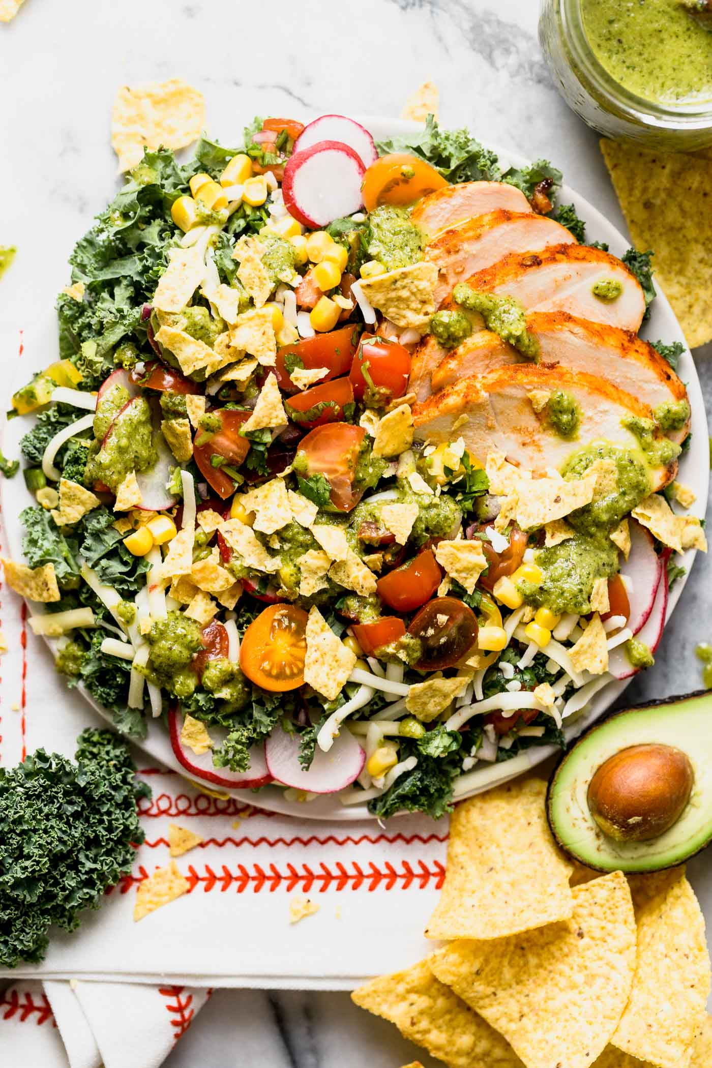 a healthy kale taco salad with chipotle lime chicken, roasted jalapeno vinaigrette, black beans, corn, pepper jack cheese, and a quick pico de gallo. this lightened-up take on a taco salad will be your new favorite! #playswellwithbutter #healthyrecipe #mealprep #healthyrecipe #kale #tacosalad #saladrecipe