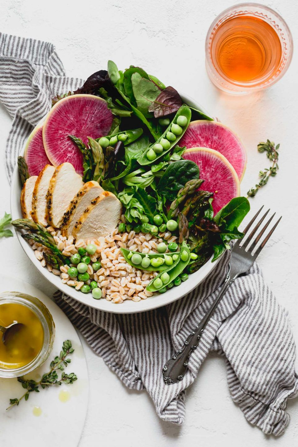 a healthy & seasonal springtime grain bowl with farro, asparagus, spring peas, greens, herbed chicken & a simple homemade lemon vinaigrette. this spring goddess grain bowl recipe is totally wholesome, meal prep friendly, & comes together in 30 minutes or less. the perfect easy weeknight dinner for this spring! #grainbowl #healthygrainbowl #saladrecipe #mealpreprecipe #springrecipe #asparagus #springpeas