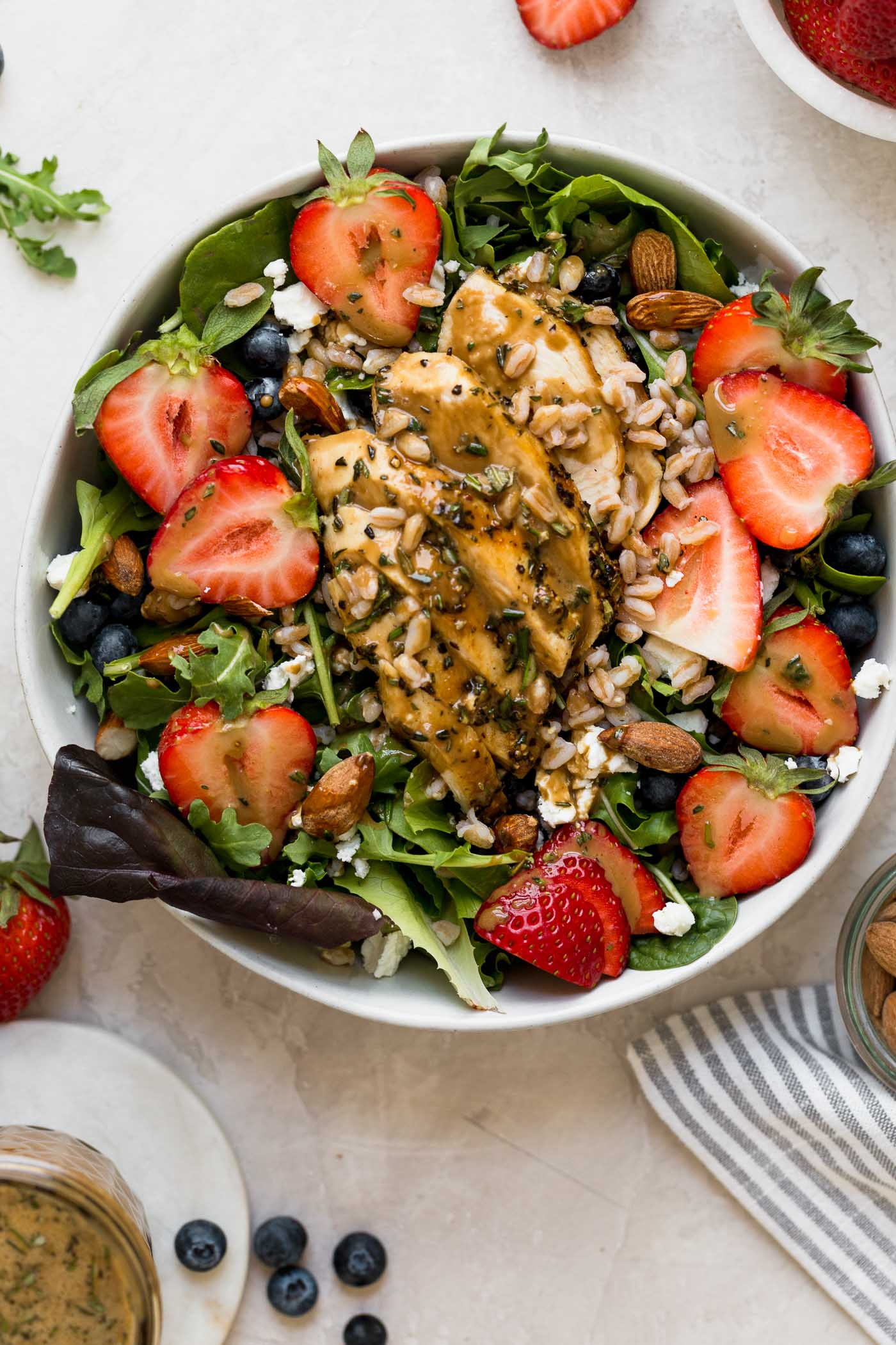an easy & healthy strawberry salad just in time for spring!!! this strawberry salad is loaded with sweet strawberries & blueberries, tangy goat cheese, chopped almonds, farro, and gets topped with simple grilled chicken breast and drizzles of the most amazing homemade maple balsamic vinaigrette. the perfect healthy salad for meal prep, an easy weeknight dinner, or for summer entertaining! #playswellwithbutter #saladrecipe #strawberrysalad #healthyrecipe #lowcarbrecipe #balsamicvinaigrette