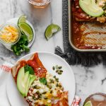 an easy & healthy chicken enchilada recipe perfect for weeknight cooking! these weeknight chicken enchiladas have a filling of pulled chicken, bell pepper sweet onion, black beans, & cheese, and get covered in the easiest blender enchilada sauce made from ancho chiles. the only thing missing is a couple of margaritas! #playswellwithbutter #chickenenchiladas #easychickenenchiladas #enchiladasrecipe #healthyenchiladas #mexicanfoodrecipes #homemadenchiladasauce #enchiladasaucerecipe #easydinnerrecipe #healthydinnerrecipe #mealpreprecipe