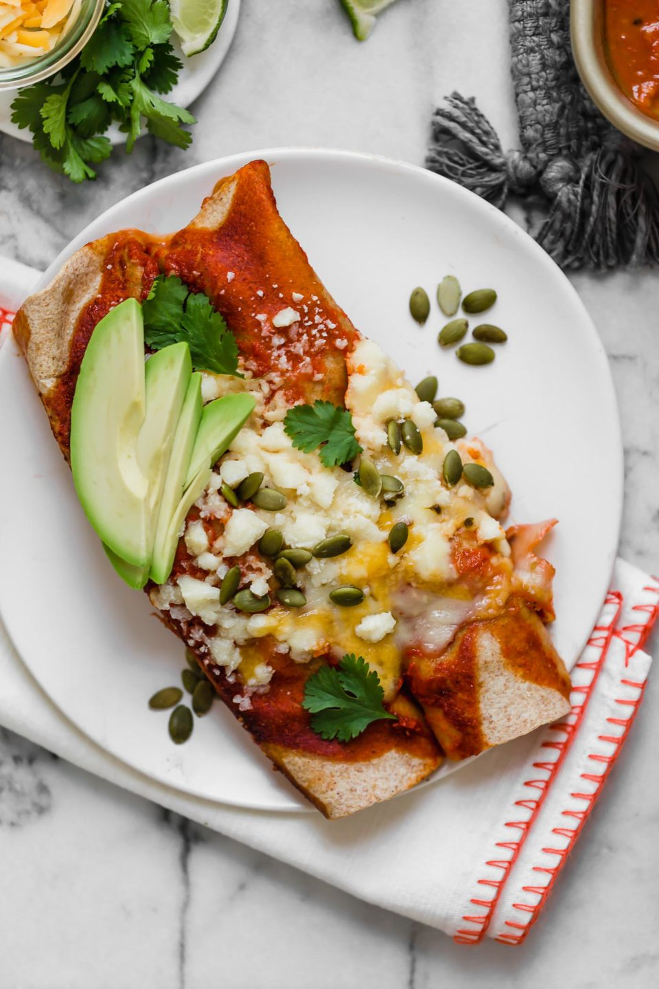 Two enchiladas sit on top of a white dinner plate. The enchilada is topped with sliced avocado, cheese, and pepitas. The plate sits on top of a white napkin with red stitching along the edges and the napkin & plate sit on top of a white & gray marbled surface.