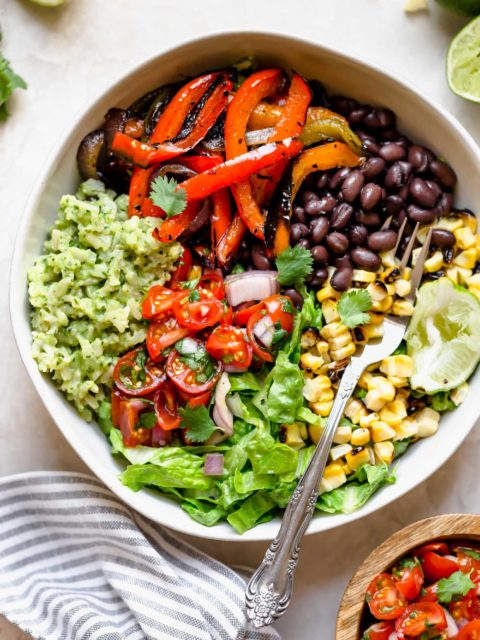 these easy & healthy grilled veggie burrito bowls are loaded with flavor! grilled peppers, onions, & sweet corn get paired with black beans & served with green rice - brown rice that's tossed in a creamy avocado sauce. move over chipotle! wholesome, plant-based, naturally vegan & gluten-free, & meal prep-friendly! & #playswellwithbutter #veggieburritobowl #healthyburritobowlrecipe #easyrecipe #healthyrecipe #mealpreprecipe #grilledvegetables #greenrice #vegetarian #plantbased #vegan #easyvegandinnerrecipe #glutenfree #easyglutenfreereceipe
