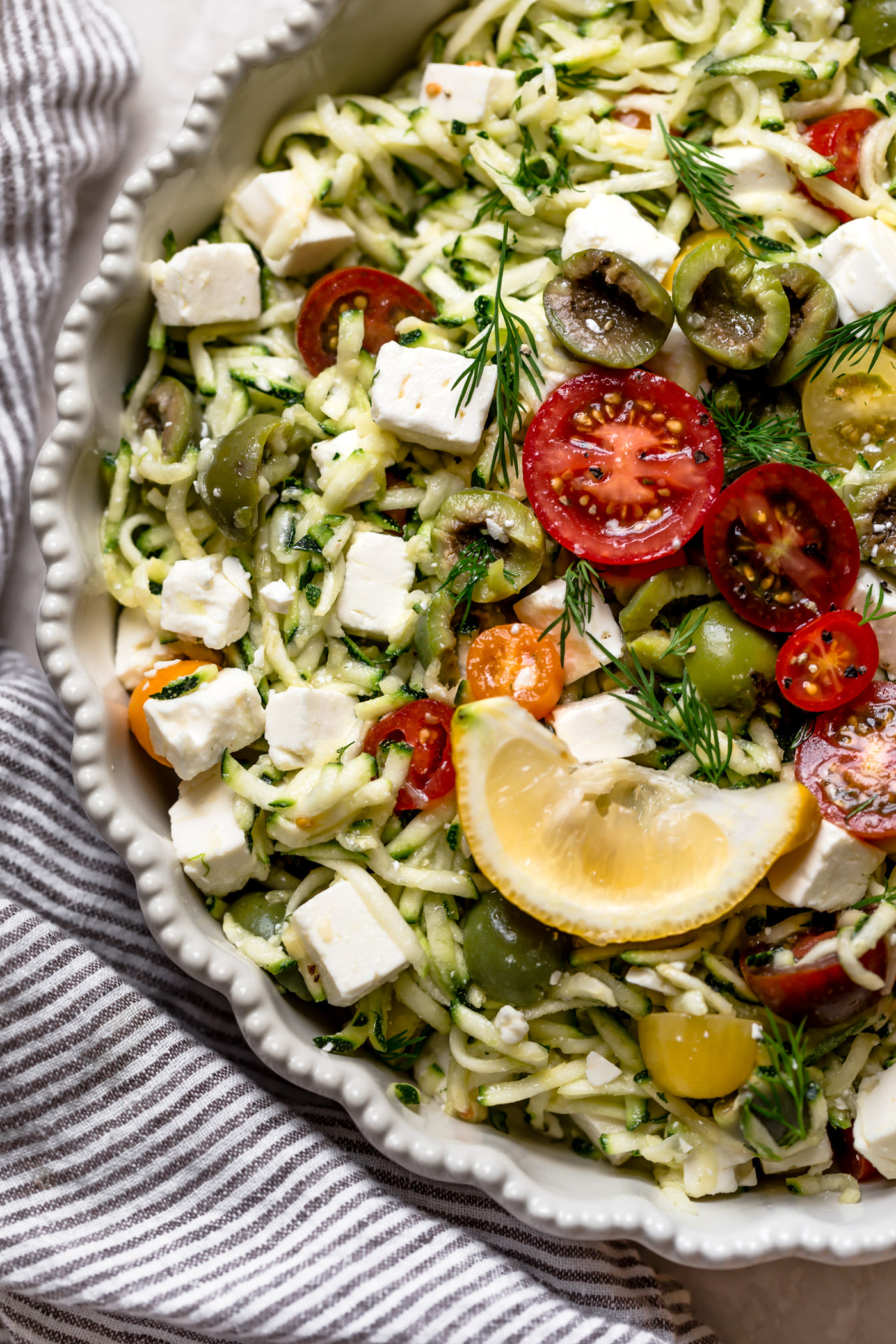 a fresh, fast, & light summertime grated zucchini salad! this easy salad has simple summer ingredients like shredded zucchini, tomatoes, castelvetrano olives, & tangy feta cheese. great for an easy weeknight dinner or side dish, or perfect for feeding a crowd at summer parties & BBQs! vegetarian, naturally gluten-free, low-carb, raw, totally healthy & fresh! #playswellwithbutter #zucchinisalad #gratedzucchini #zucchinirecipe #shreddedzucchini #summersalad #sidedish #rawsalad #lowcarbrecipe