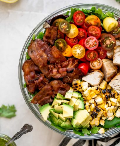 a light & fresh blt salad for summer loaded with bacon, cherry tomatoes, sweet corn, avocados, grilled chicken, & an easy cilantro basil vinaigrette. this blt salad recipe is hearty, but super fresh, making it the perfect easy summer dinner. naturally gluten-free & perfect for meal prep! #playswellwithbutter #bltsalad #saladrecipe #dinnersalad #summersalad #glutenfree #easyglutenfreerecipes