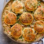 skillet chicken pot pie. an easy homemade chicken pot pie recipe made entirely in a cast iron skillet! this skillet chicken pot pie has the creamiest filling loaded with carrots, potatoes, & shredded chicken & an extra flaky biscuit topping with herbed garlic butter. easy enough for busy weeknights, & comforting enough for cold winter nights, this skillet chicken pot pie is the perfect comfort food recipe! #playswellwithbutter #chickenpotpiewithbiscuits #skilletchickenpotpie #easychickenpotpie #castironskilletrecipes