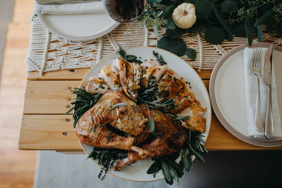 A plate of carved Thanksgiving turkey sits on a wooden table, amongst neutral table settings and a centerpiece made of eucalyptus & mini white pumpkins.