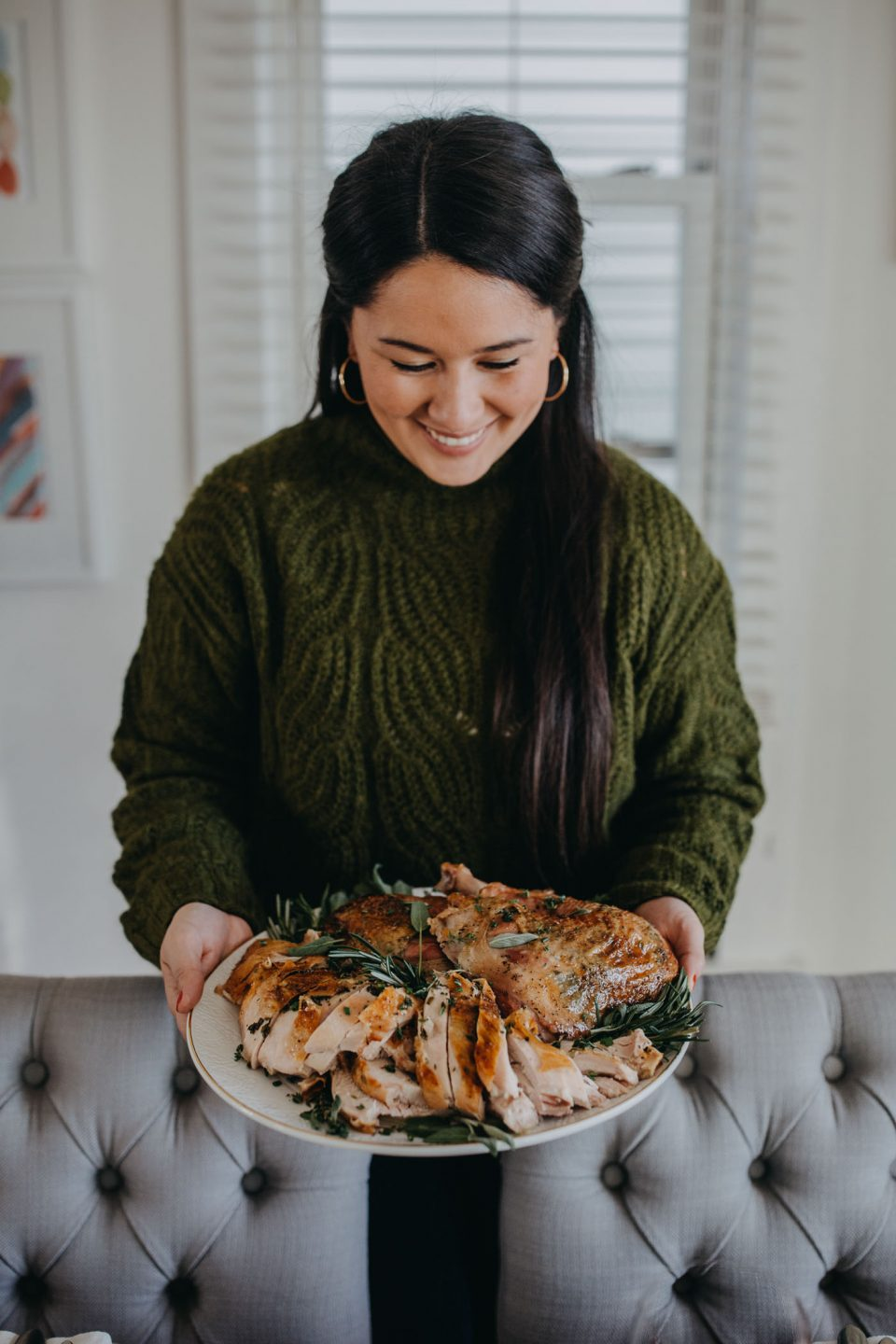 Dark-haired woman in a green sweater holds a plate of carved turkey, in front of a festive tablescape & a full Thanksgiving dinner spread.