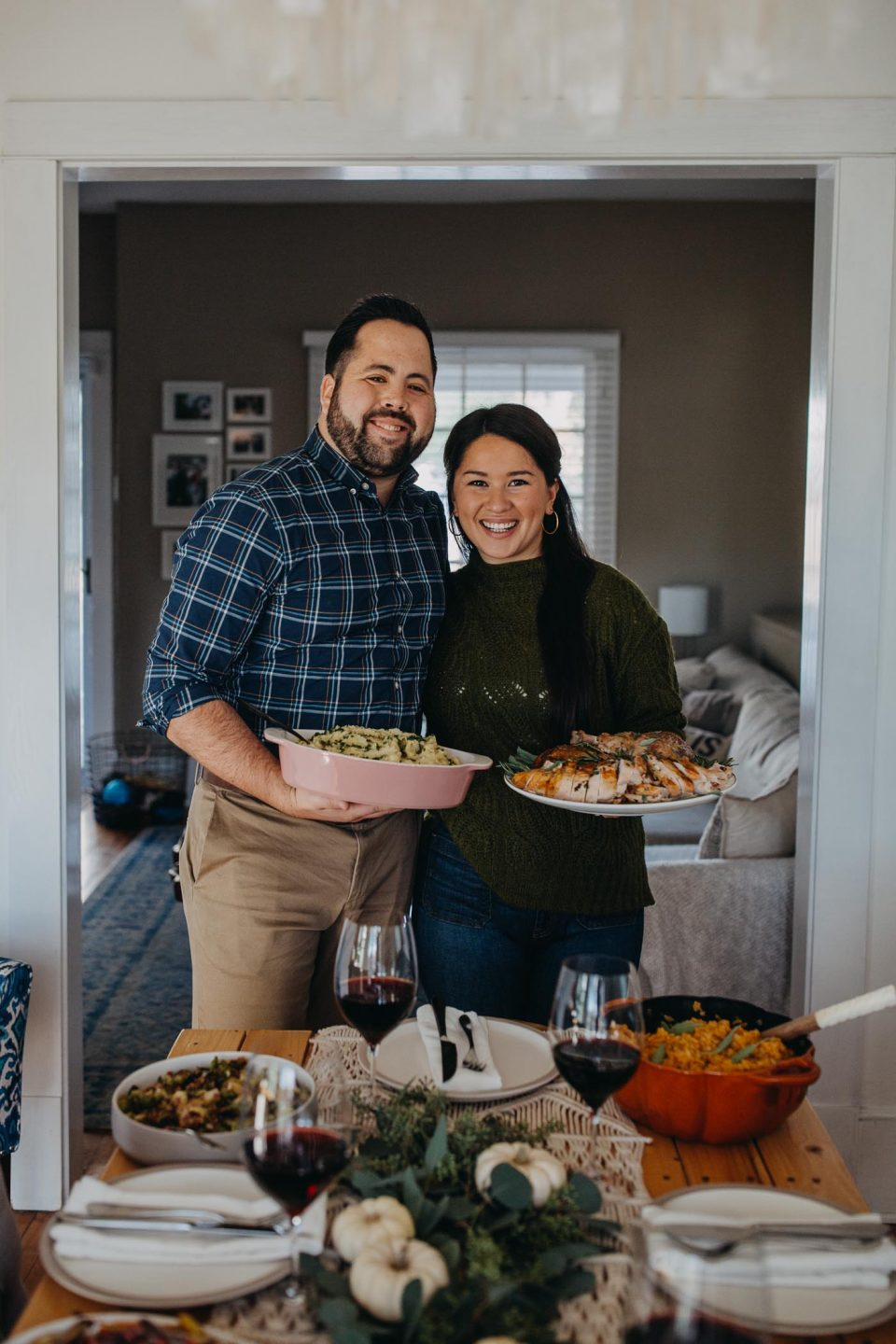 Dark-haired woman in a green sweater holds a plate of carved turkey. Dark-haired man in a blue plaid shirt holds a pink casserole dish filled with buttermilk mashed potatoes. They stand side-by-side in front of a festive tablescape & a full Thanksgiving dinner spread.