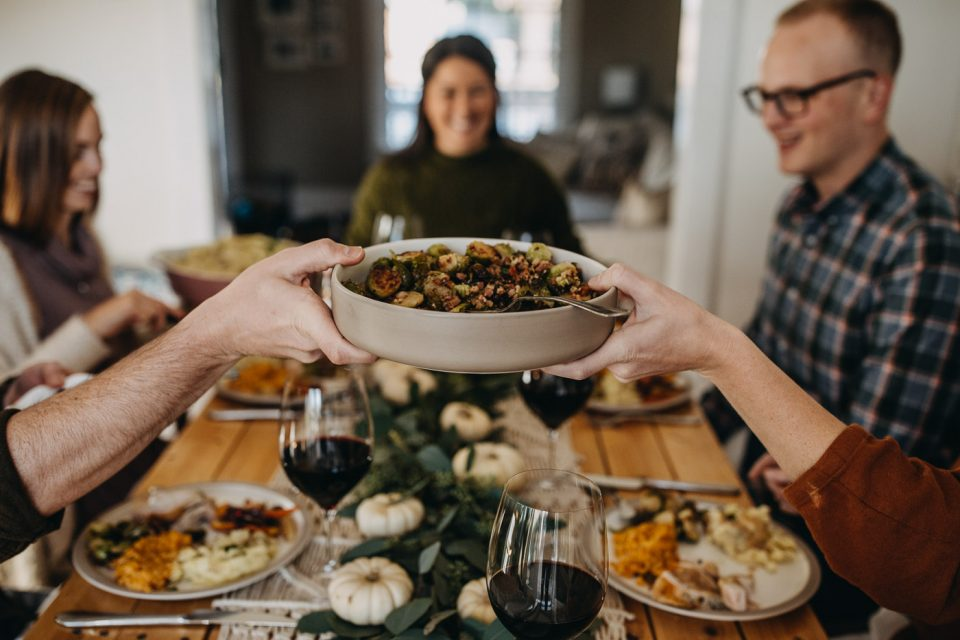 A bowl of brussels sprouts being passed across a Thanksgiving table.