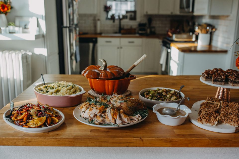 Thanksgiving dinner spread (roasted turkey, carrots, mashed potatoes, brussels sprouts, gravy, desserts) arranged on a kitchen counter in a bright, white kitchen.