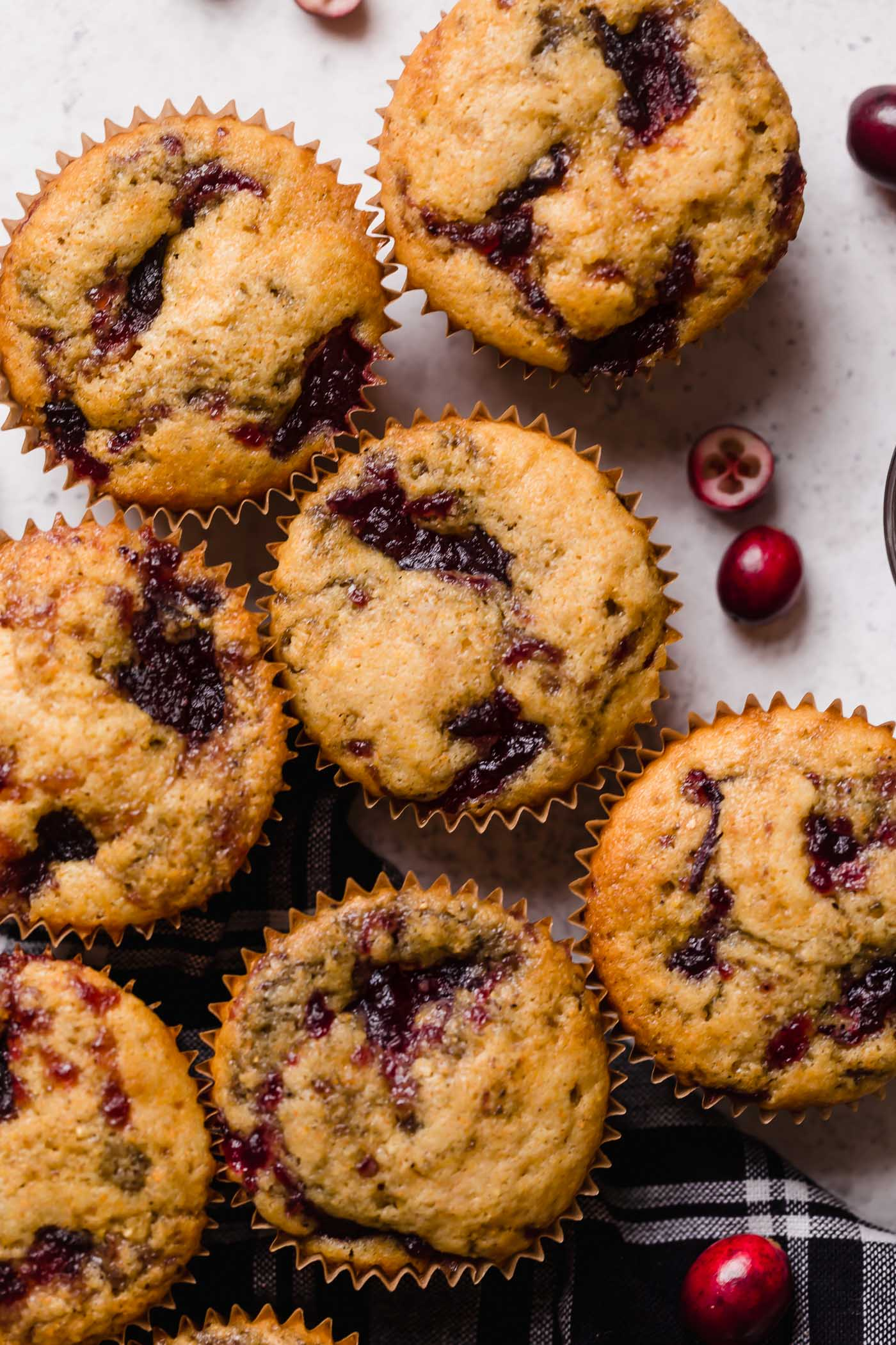 swirled cranberry cornbread muffins. these cranberry cornbread muffins have cranberry sauce swirled throughout them, making them a gorgeously festive for the holiday season! move over parker house rolls, these cranberry cornbread muffins will earn a permanent spot on your thanksgiving & friendsgiving menus from here on out! #playswellwithbutter #cranberrycornbread #cornbread #cornbreadmuffins #thanksgivingsidedish #friendsgiving #thanksgivingsides #easythanksgivingsides