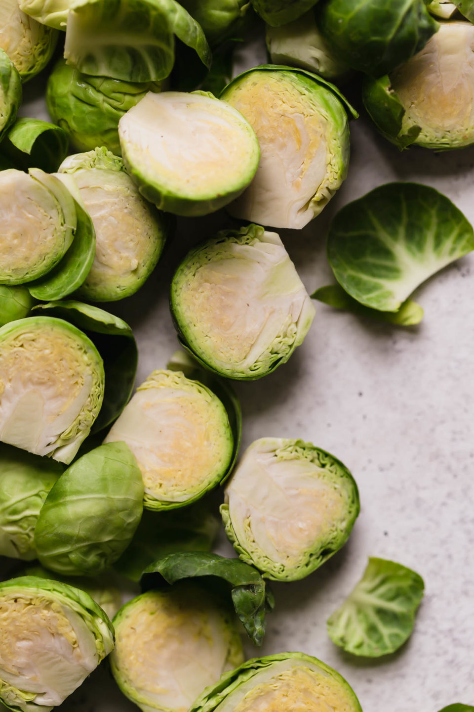 Trimmed brussels sprouts arranged on a white backdrop. The brussels sprouts are halved lengthwise.