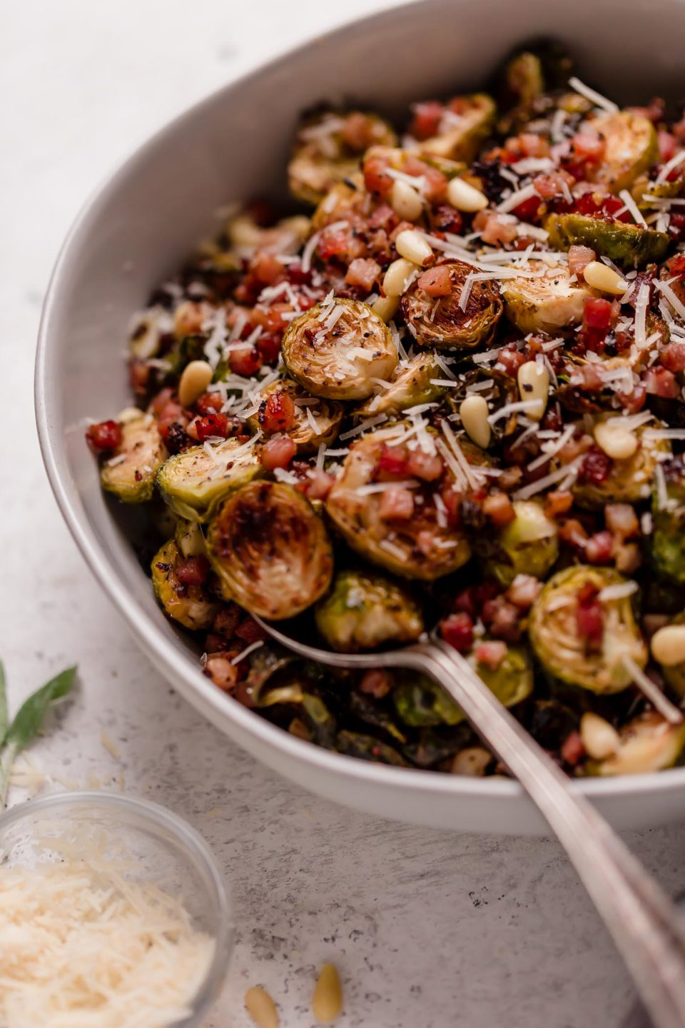 Roasted brussels sprouts in a large white serving bowl, with pancetta, pine nuts and finely shredded parmesan. The bowl is on a white surface, next to a small bowl of finely grated parmesan & some fresh sage leaves.