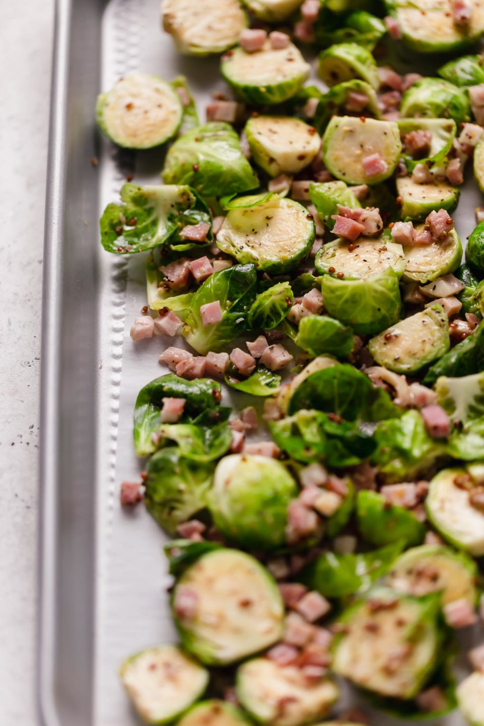 The brussels sprouts with pancetta arranged on a parchment-lined baking sheet for roasting.