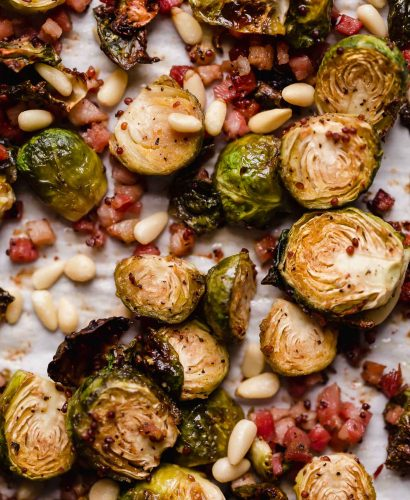 Maple roasted brussels sprouts with pancetta & pine nuts arranged on a parchment-lined baking sheet. The brussels sprouts are beautifully golden brown, having been roasted.