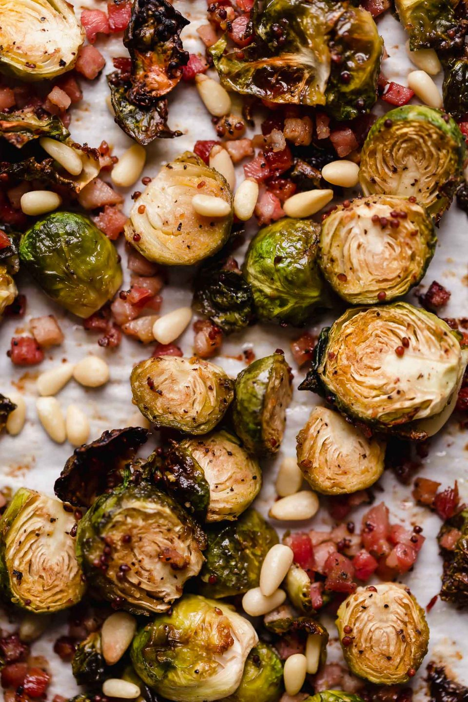 Maple mustard roasted brussels sprouts with pancetta & pine nuts arranged on a parchment-lined baking sheet. The brussels sprouts are beautifully golden brown, having been roasted.