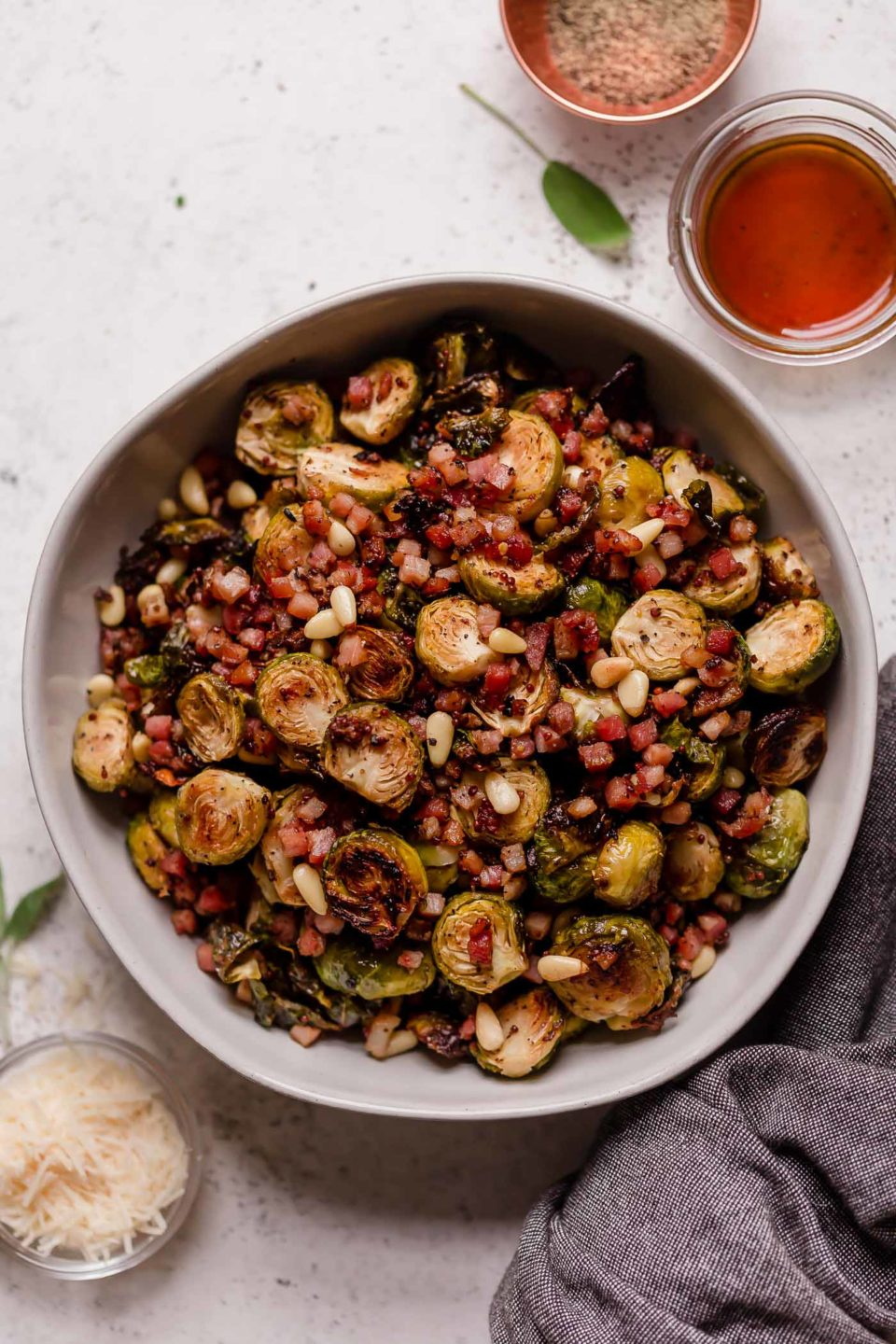 Maple mustard roasted brussels sprouts with pancetta, pine nuts, & parmesan in a large serving bowl. The bowl is on a white backdrop, surrounded by smaller bowls containing parmesan cheese, pine nuts, & mustard.