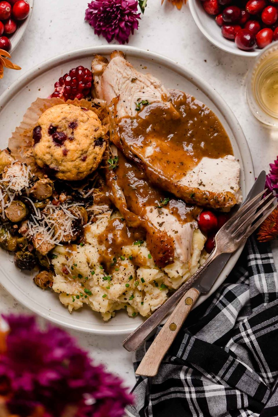 A white plate full of Thanksgiving foods including Maple Mustard Roasted Brussels Sprouts topped with parmesan cheese, a single Swirled Cranberry Cornbread Muffin, two large slices of Maple Glazed Spatchcock Turkey and Roasted Garlic Mashed Potatoes topped with gravy. The plate has a fork & a knife resting on it and is surrounded by purple flowers a plaid dinner napkin and bowls of fresh cranberries.