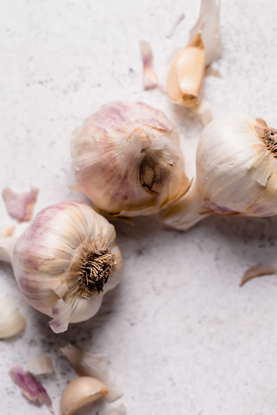 3 heads of garlic on a white surface to make roasted garlic for roasted garlic buttermilk mashed potatoes.