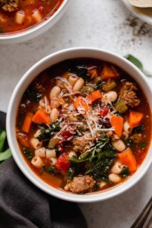 a hearty italian minestrone soup recipe, made with sausage, veggies, beans, kale, & a garlic & herb infused broth. this minestrone soup is comforting, rich, & the perfect cozy recipe to make all winter long. the ultimate minestrone soup! #playswellwithbutter #minestronesoup #heartysouprecipes #heartymeals #souprecipes #comfortfood #comfortfooddinners #soup #italianrecipes #italiansoup