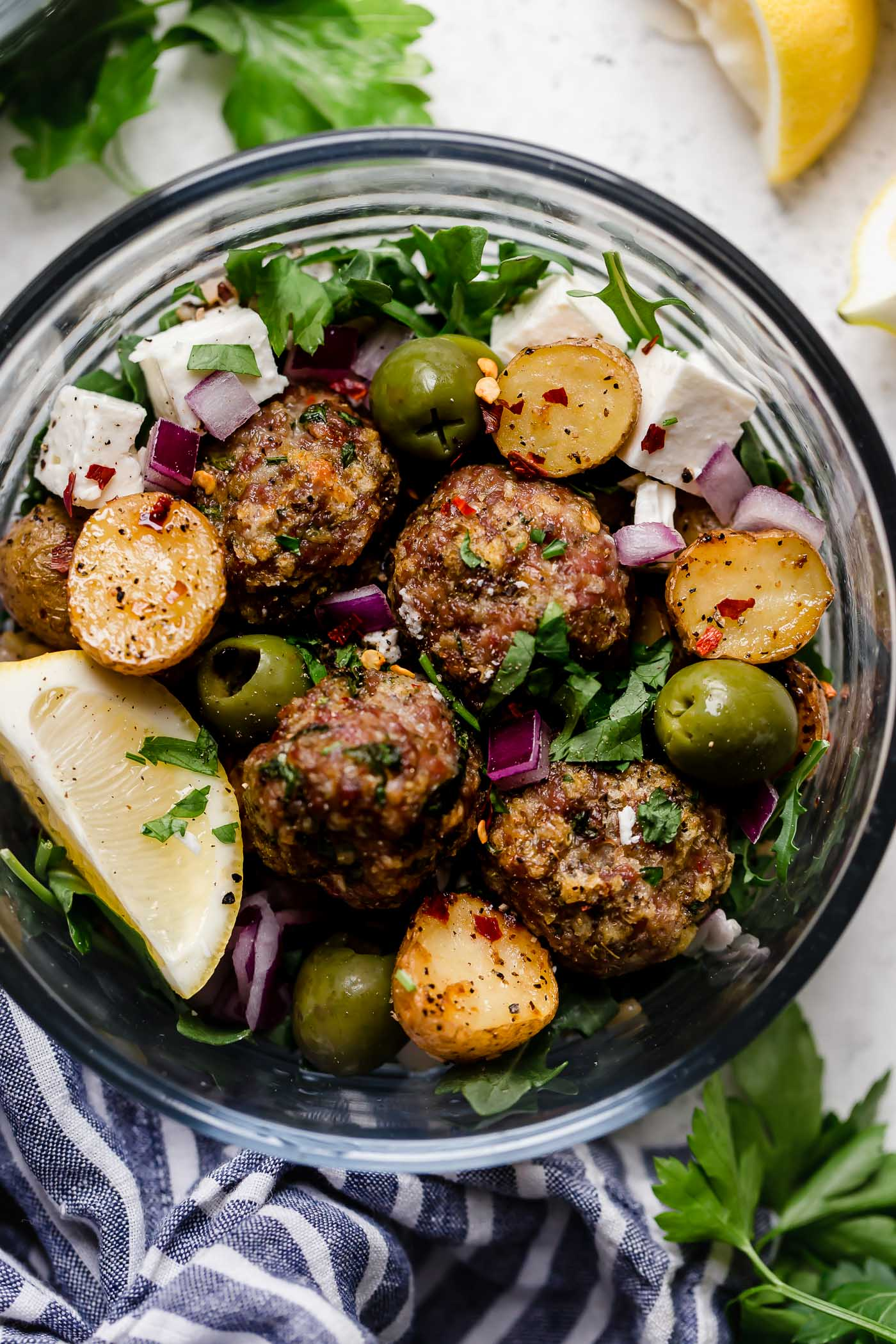 the easiest juicy & tender baked lamb meatballs, made with panko breadcrumbs, lemon, parsley, oregano & cumin, served on top of a seriously healthy meal prep bowl with lemony Greek roasted potatoes, greens, feta, olives, & homemade Romesco sauce. an easy & satisfying meal prep recipe for lunches all week long! #playswellwithbutter #lambmeatballs #bakedlambmeatballs #greeklambmeatballs #groundlamb #mealpreprecipes #mealpreprecipesfortheweek #mediterraneandiet #healthybowlsrecipe